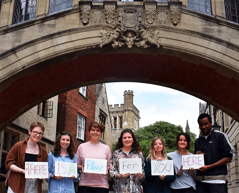 Students standing in Oxford University hold a sign that says 'There is a place for you here' sign